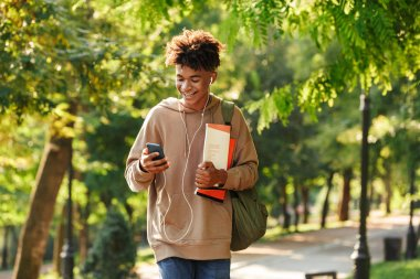 Happy young african guy with backpack walking at the park, listening to music with earphones