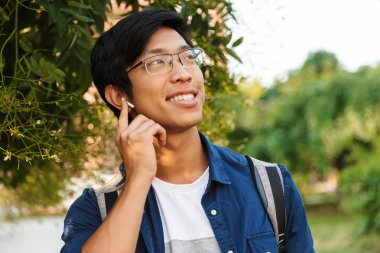 Image of Smiling asian male student in eyeglasses listening music and looking away outdoors