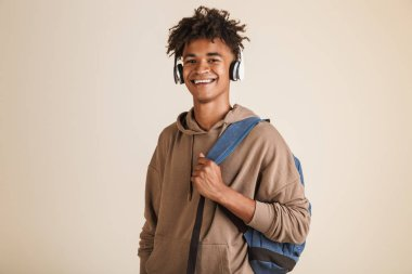 Portrait of a cheerful young afro american man dressed in hoodie with headphones carrying backpack isolated