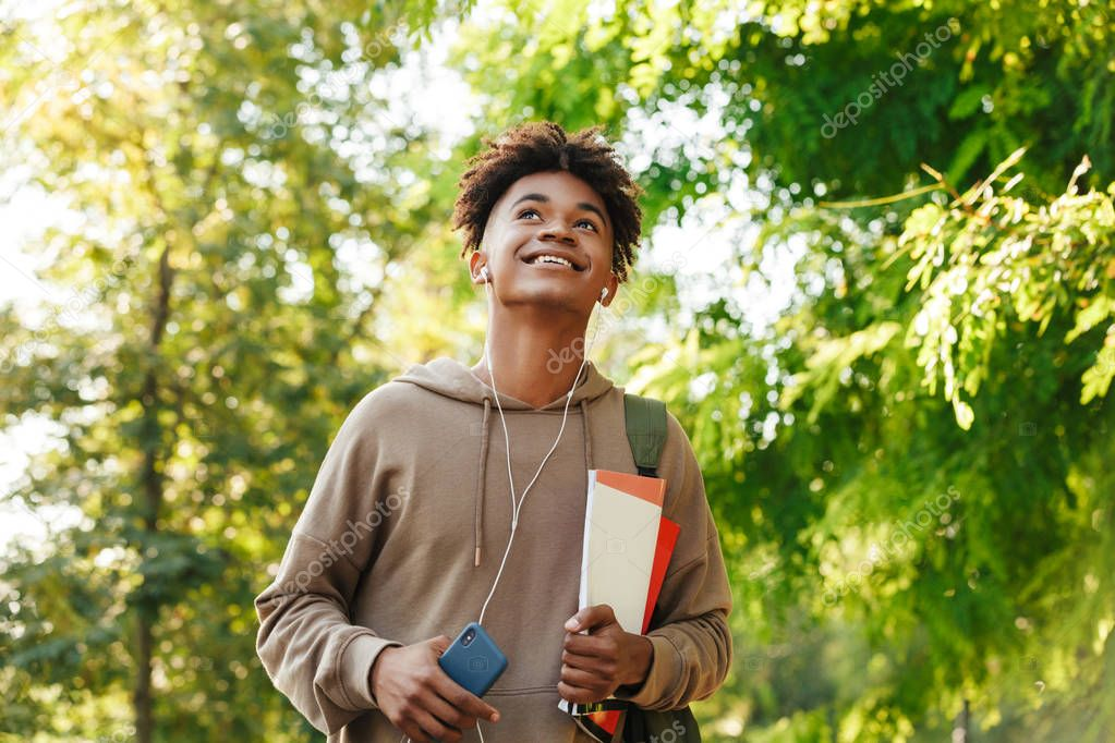 Joyful young african guy with backpack walking at the park, listening to music with earphones