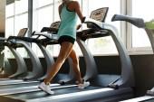 Fotografie abgeschnittenes Bild einer Sportlerin beim Training auf dem Laufband in der Nähe des Fensters im Fitnessstudio