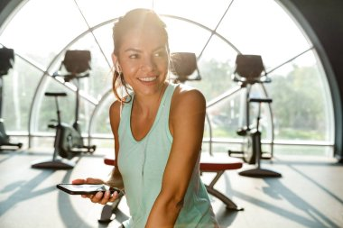 Cheerful sports woman in earphones holding smartphone and looking away while being in gym