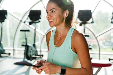 Happy sports woman in earphones holding smartphone and looking away while being in gym