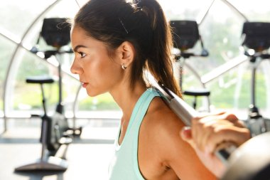 Side view of motivated sports woman doing exercise with barbell in gym