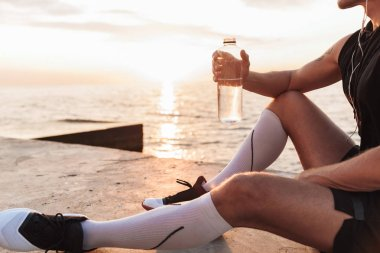Cropped image of handsome strong young sportsman outdoors at the beach listening music with earphones drinking water.