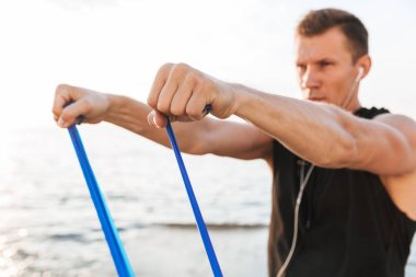 Picture of strong young sportsman outdoors at the beach make sport exercises with equipment.