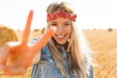 Fotografia Beautiful young blonde girl in headband at the wheat field, showing peace sign