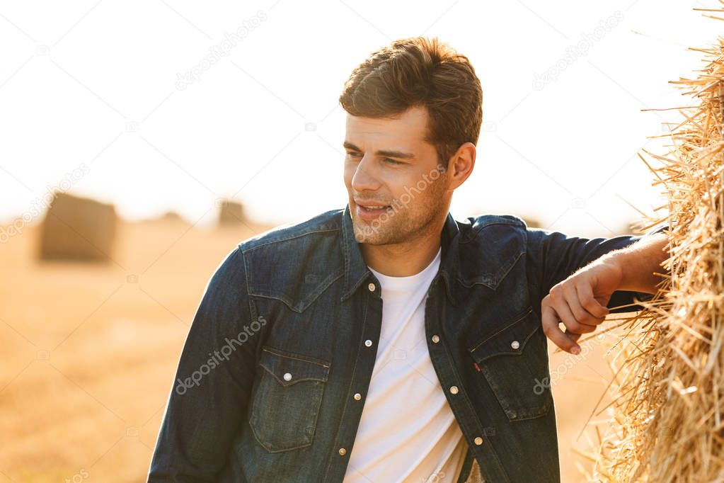 Image of handsome man 30s walking through golden field and standing near big haystack during sunny day
