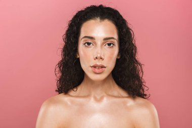 Portrait of pretty beautiful young woman with healthy skin posing isolated over pink background looking camera.