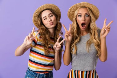 Two pretty young girls friends in summer hats standing isolated over violet background, showing peace
