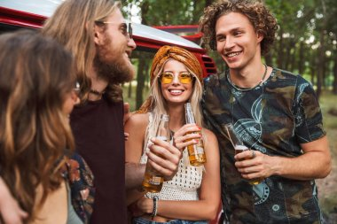 Group of attractive hippies men and women smiling and drinking beer near vintage minivan into the nature