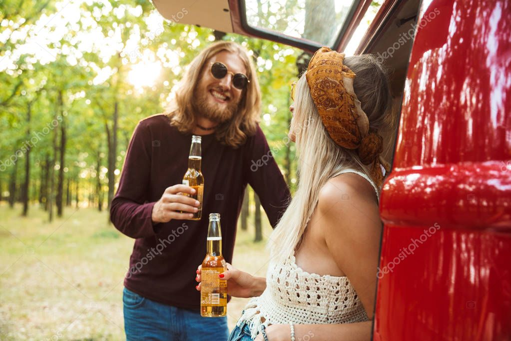 Photo of attractive hippie couple man and woman smiling and drinking beer in forest near retro minivan