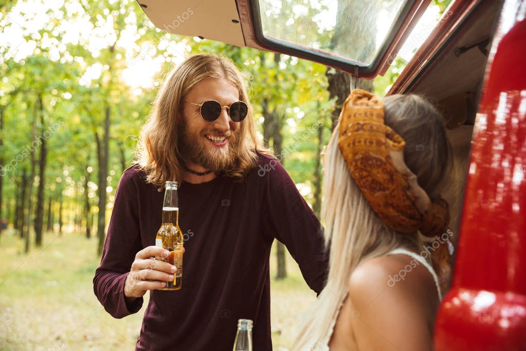 Photo of joyous hippie couple man and woman smiling and drinking beer in forest near retro minivan