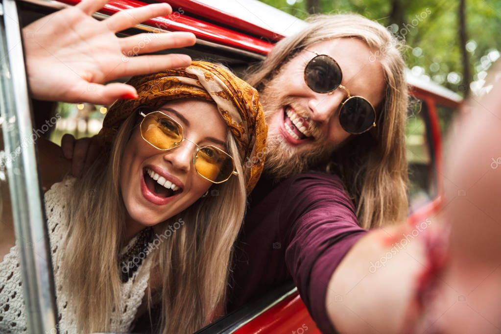 Photo of happy hippie travelers man and woman smiling and sitting in retro minivan in forest