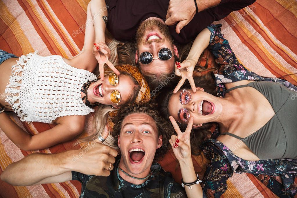 Photo of attractive hippies guys and girls laughing and lying on blanket in circle outdoor