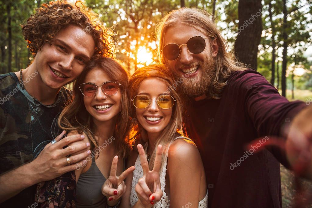 Photo of beautiful hippie people men and women smiling and taking selfie in forest