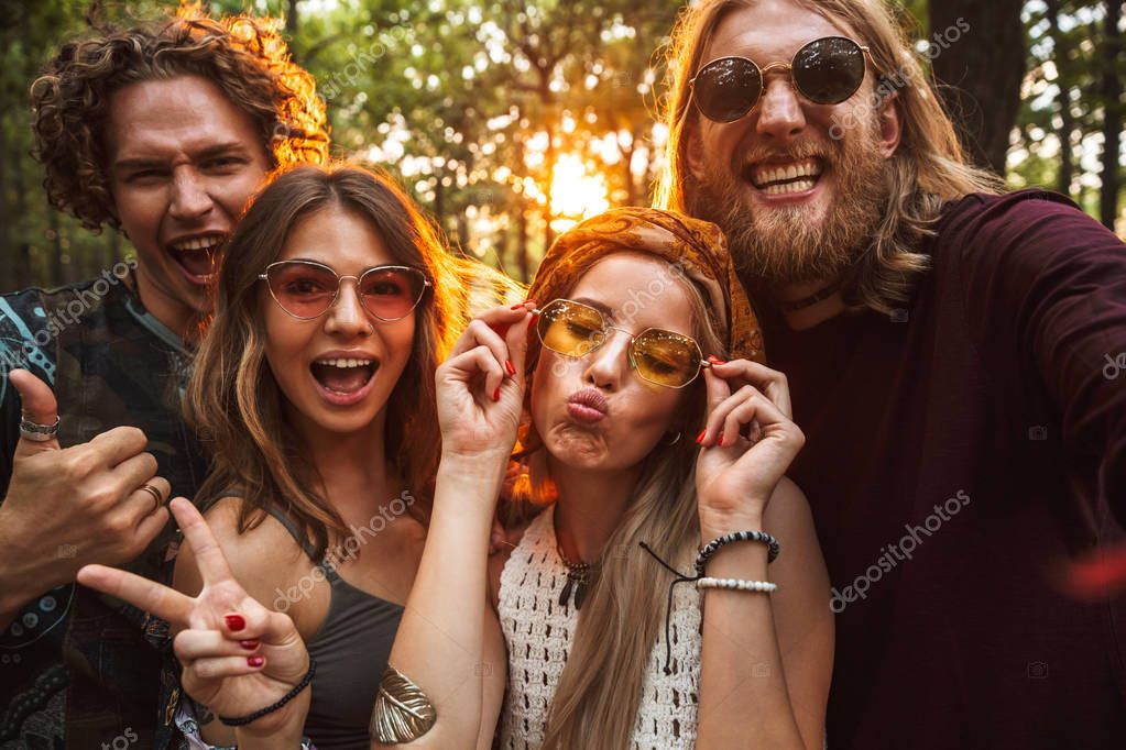 Photo of friendly hippie people men and women smiling and taking selfie in forest