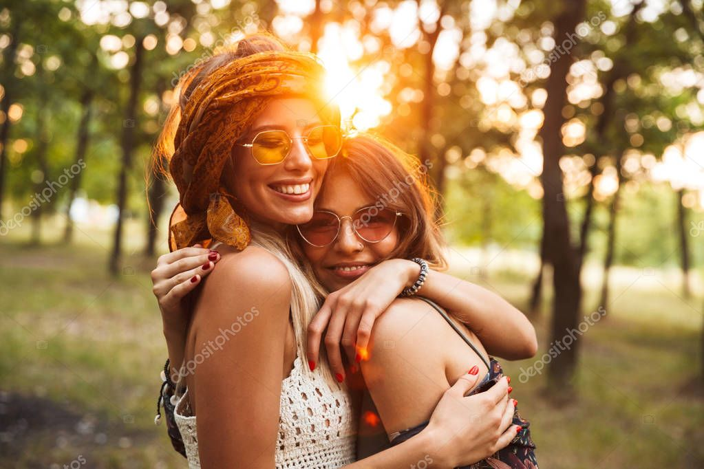 Photo of two caucasian hippie girls smiling and hugging each other while walking in forest