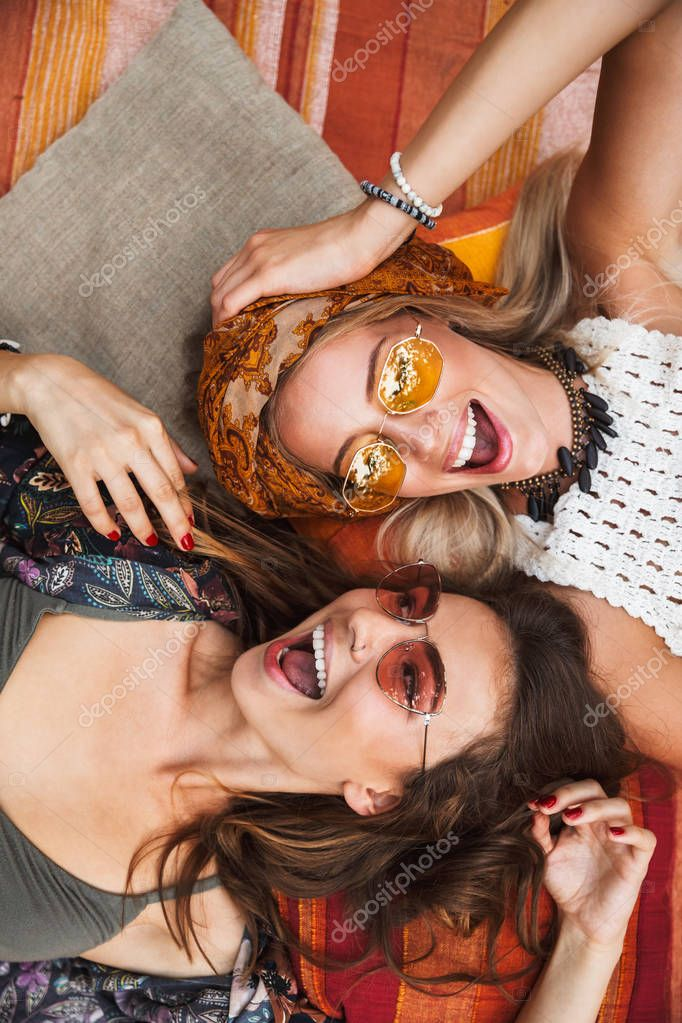 Photo from top of two lovely hippie women smiling and lying on blanket outdoor head to head
