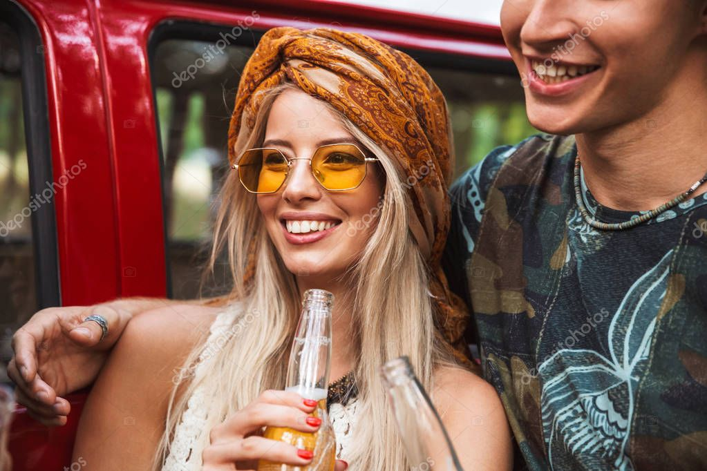 Beautiful hipster couple man and woman smiling and drinking beer near vintage minivan into the nature
