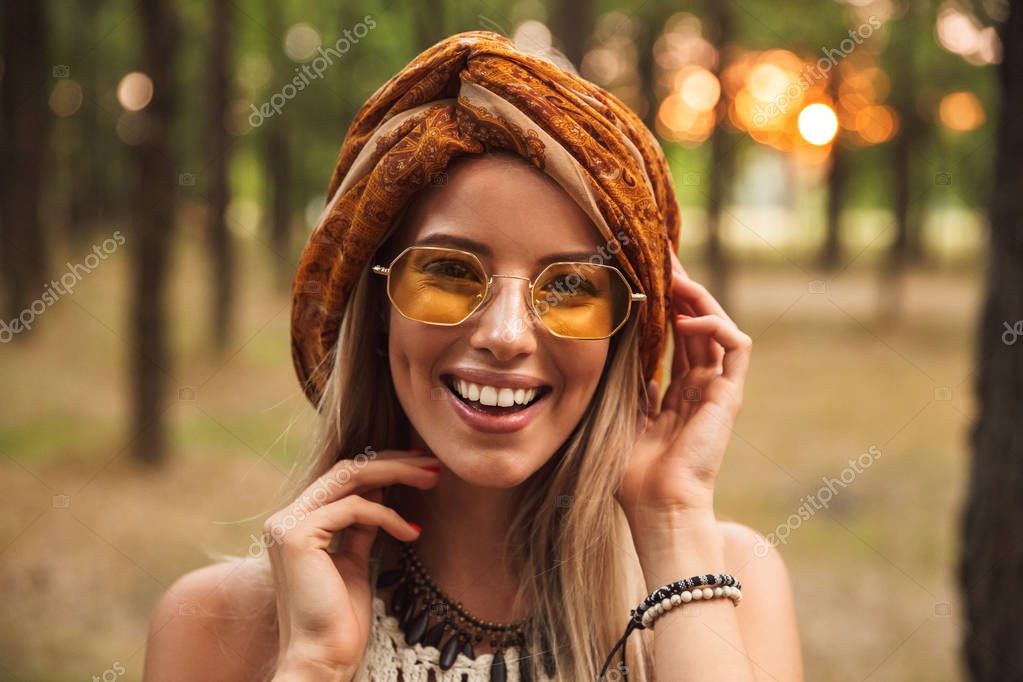 Photo of happy hippy woman wearing stylish accessories smiling while walking in forest