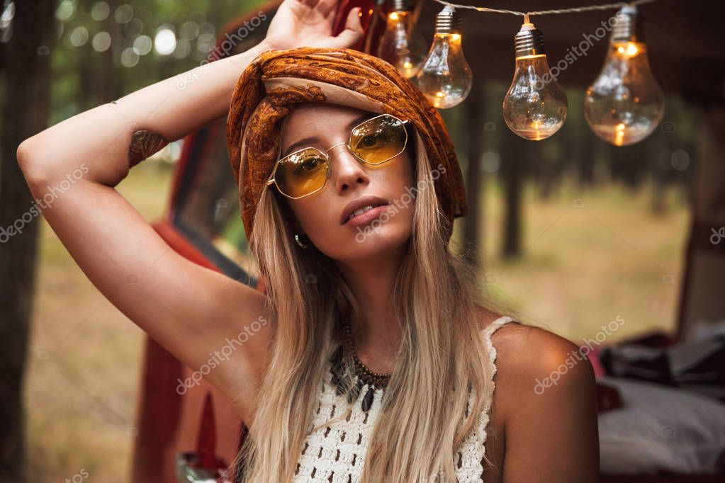 Photo of beautiful hippie woman wearing stylish accessories looking forward while resting in forest camp