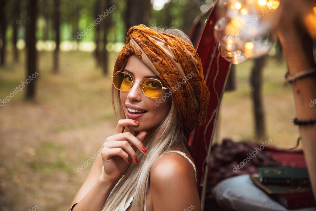 Photo of caucasian hippy woman wearing stylish accessories looking forward while resting in forest camp