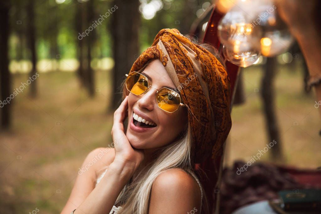 Image of blond cute woman wearing vintage accessories smiling while resting in forest camp
