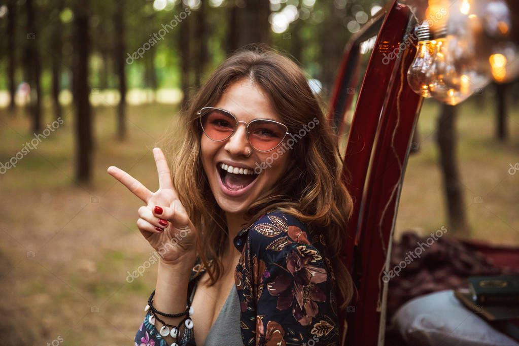 Image of attractive woman 20s wearing stylish accessories smiling while resting in forest camp