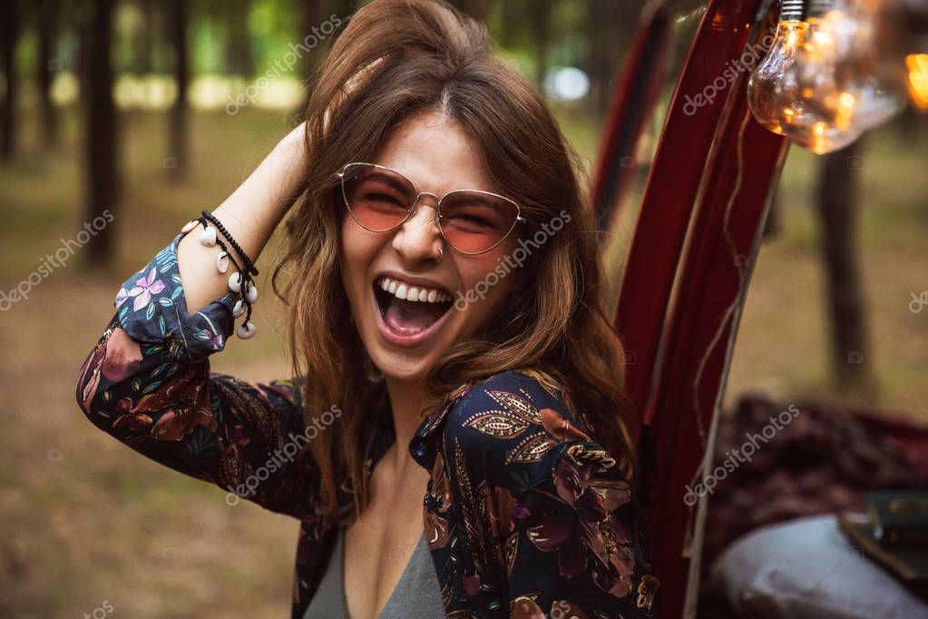 Image of joyful woman wearing hippy accessories smiling while resting in forest camp