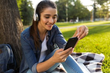 Image of amazing beautiful young woman student in the park listening music with headphones using mobile phone.