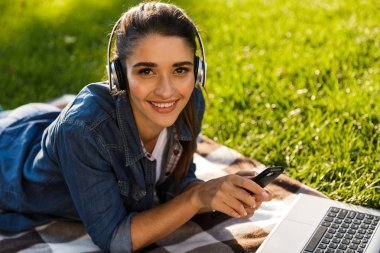 Image of amazing beautiful young woman student in the park using laptop computer listening music with headphones using mobile phone.