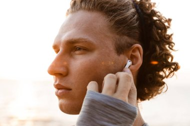Image of handsome young sports man standing on the beach listening music with earphones.