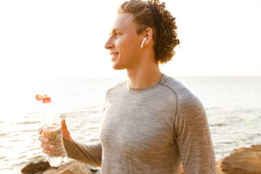 Photo of handsome young sports man standing on the beach drinking water listening music.