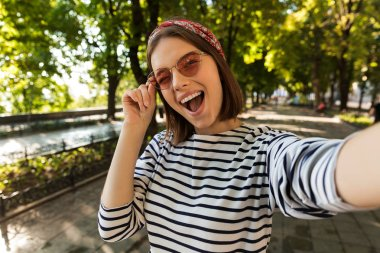 Photo of young beautiful excited cute woman outdoors take a selfie by camera winking. stock vector