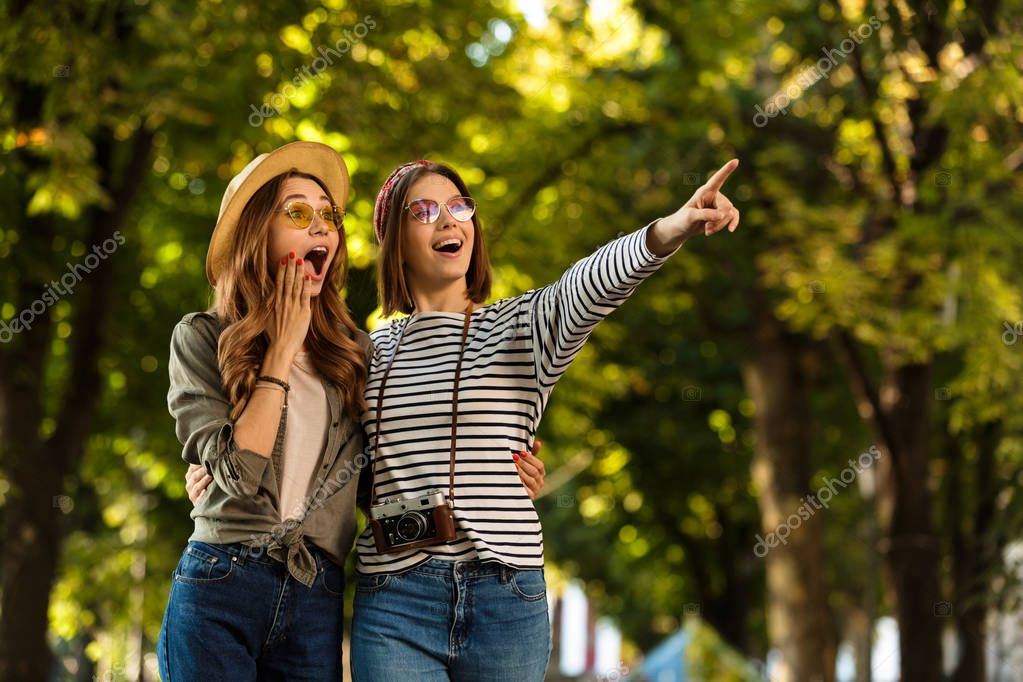Image of excited pretty young happy women friends walking outdoors with backpacks and camera pointing.