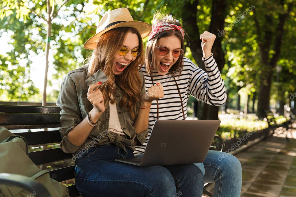 Photo of young emotional excited happy ladies friends outdoors sitting using laptop computer holding credit card.