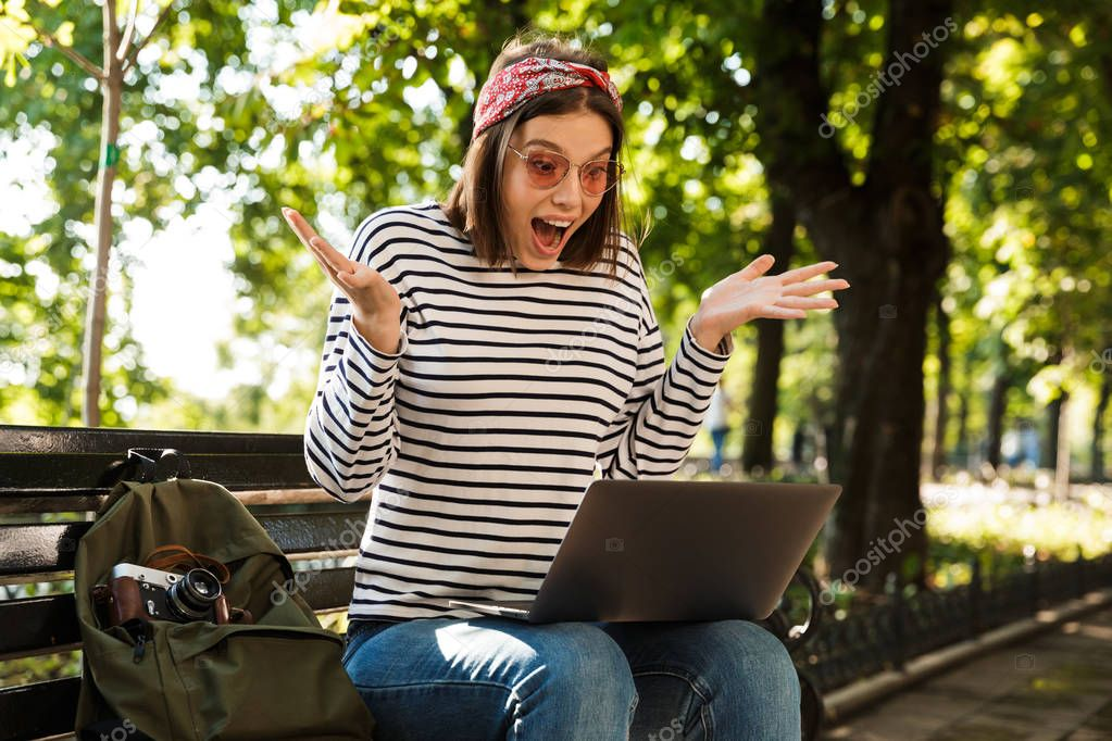 Photo of young beautiful excited happy woman outdoors sitting using laptop computer make winner gesture.