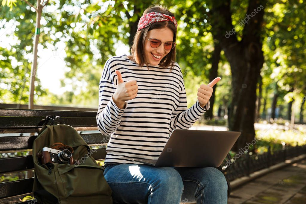 Photo of young beautiful excited happy woman outdoors sitting using laptop computer make thumbs up.