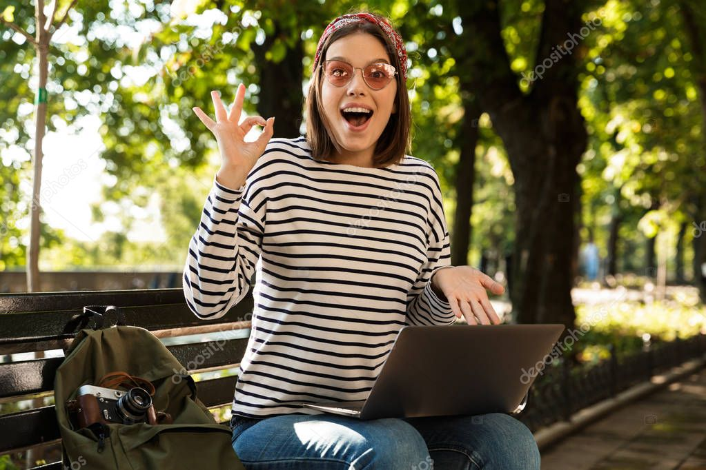 Photo of young beautiful excited happy woman outdoors sitting using laptop computer make okay gesture.