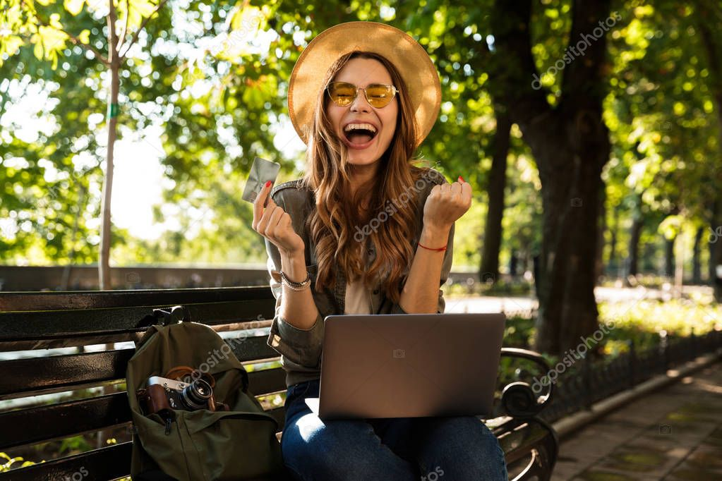 Photo of young beautiful excited happy woman outdoors sitting using laptop computer make winner gesture holding credit card.
