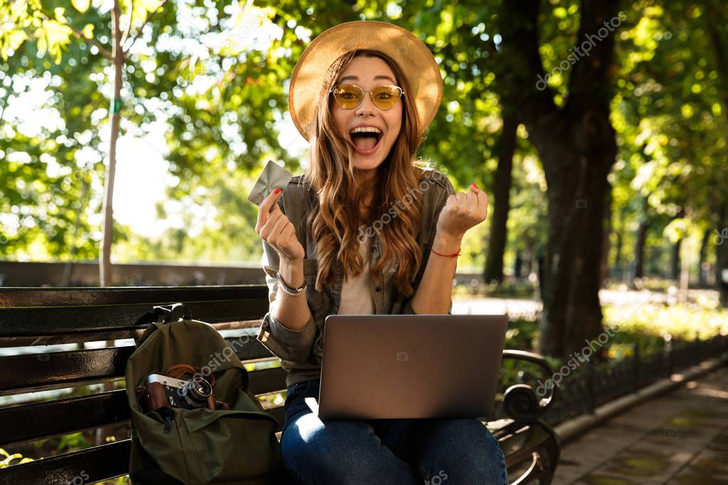 Image of young beautiful excited happy woman outdoors sitting using laptop computer holding credit card.