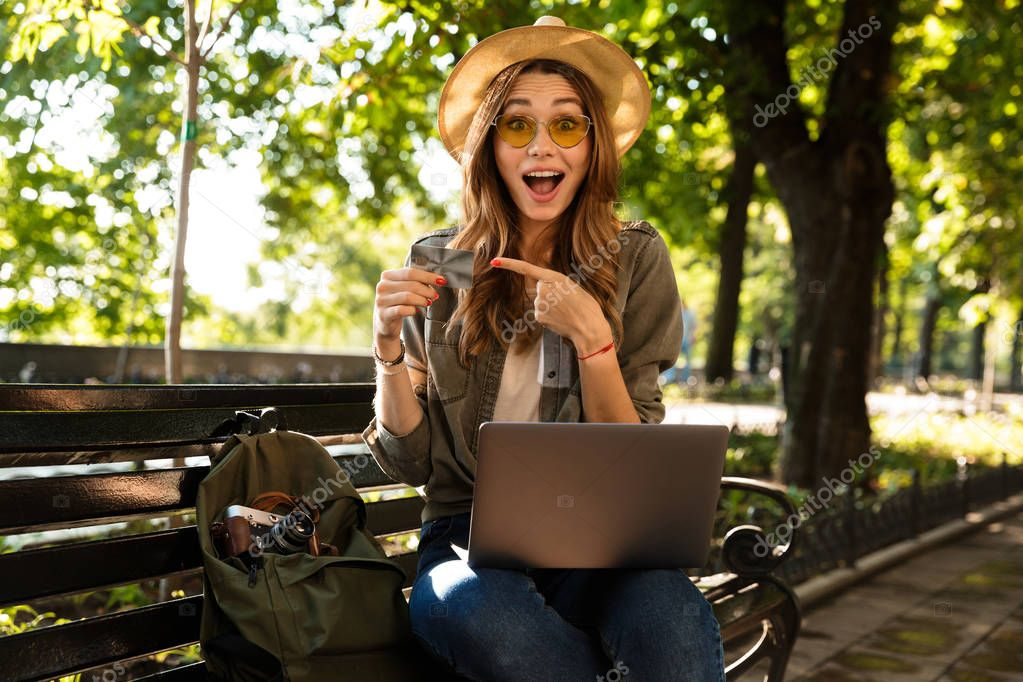 Photo of young beautiful excited happy woman outdoors sitting using laptop computer holding credit card pointing.