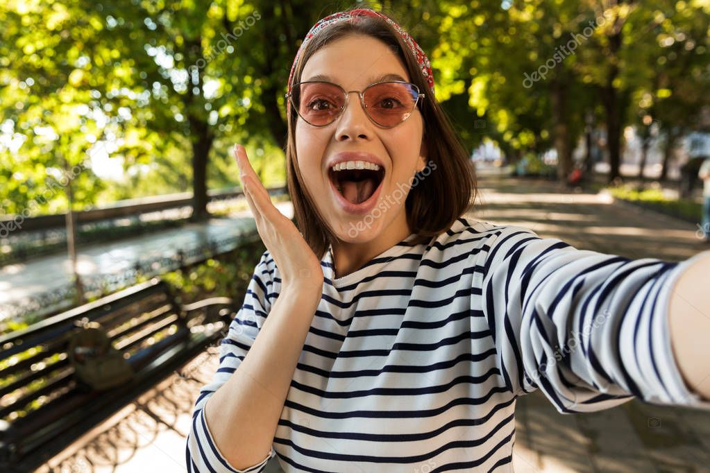 Photo of young beautiful excited shocked woman outdoors take a selfie by camera.