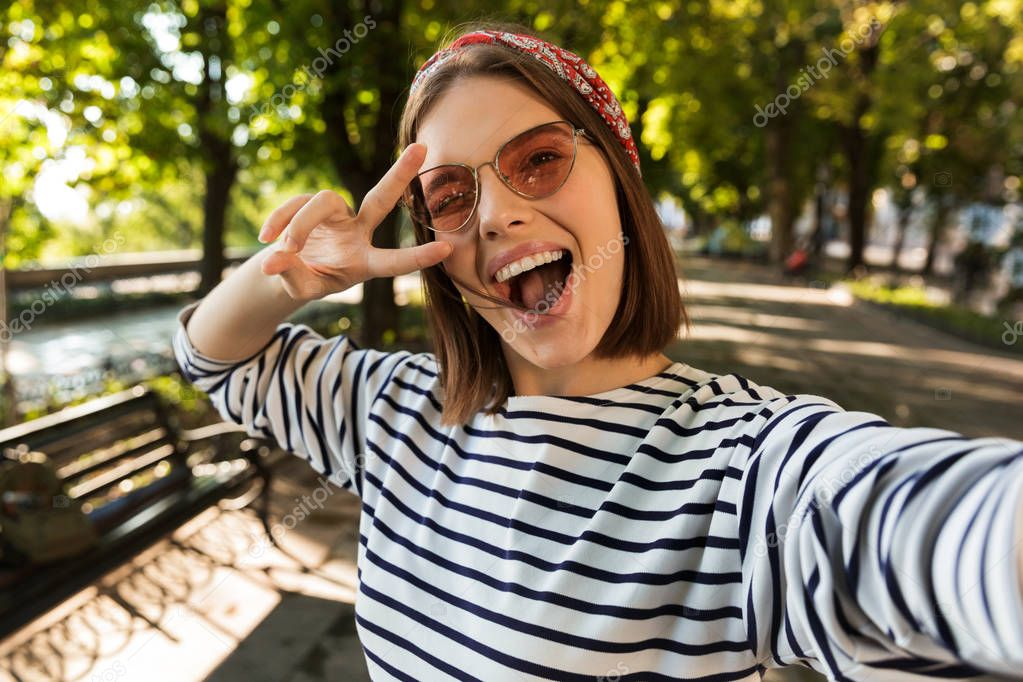 Photo of young beautiful excited happy woman outdoors take a selfie by camera showing peace gesture.