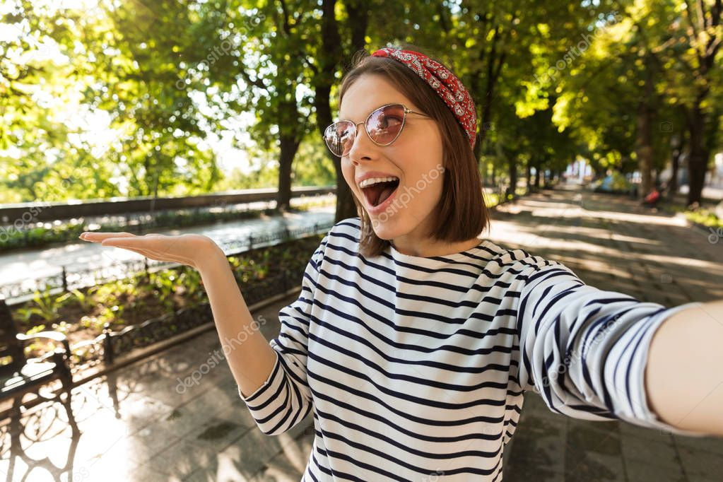 Photo of young beautiful excited shocked woman outdoors take a selfie by camera showing copyspace.
