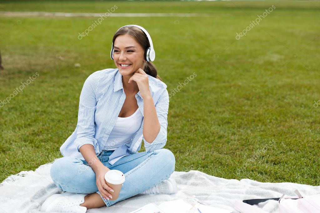 Image of beautiful young pretty woman in park outdoors listening music drinking coffee.