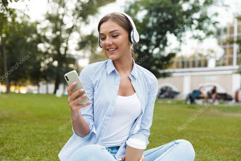 Image of beautiful young pretty woman in park outdoors listening music using mobile phone.