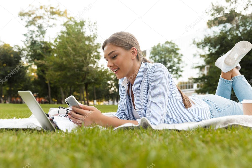 Smiling young girl spending time at the park, studying, laying on a blanket with laptop computer, using mobile phone