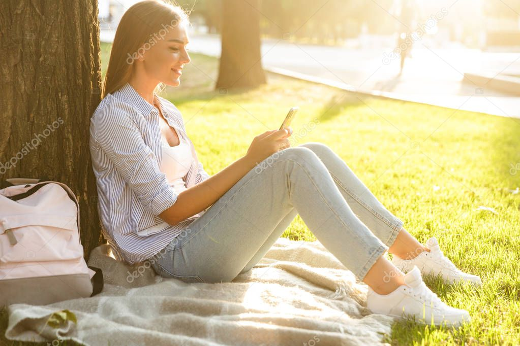 Pretty young girl spending time at the park, sitting on a grass with backpack, holding mobile phone